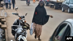 FILE - A Muslim woman walks in the Brituetterie district of Yaounde, Cameroon, July 16, 2015.