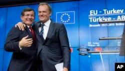 PM Turki Ahmet Davutoglu (kiri) berangkulan dengan Presiden Uni Eropa Donald Tusk pada KTT 4 jam di Brussels, Belgia Minggu (29/11).
