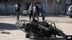 Palestinians walk near the debris of a damaged motorcycle after an Israeli airstrike in Deir al-Balah, central Gaza Strip, Sunday, Feb. 9, 2014.