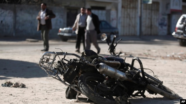 Palestinians walk near the debris of a damaged motorcycle after an Israeli airstrike in Deir al-Balah, central Gaza Strip, Sunday, Feb. 9, 2014.