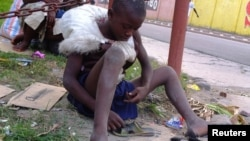 FILE - A homeless child repairs a shoe along a street in the in capital Kinshasa, in the Democratic Republic of Congo, June 2013.
