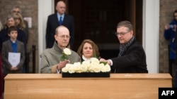 Canadian carpenter Michael Ibsen, left, a descendant of King Richard III, the last of the Plantagenet dynasty, and two other descendants place roses on the oak coffin with the remains of the monarch during a service in Leicester, England, March 22, 2015.