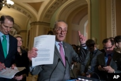 FILE - Senate Minority Leader Chuck Schumer of New York, joined by, from left, Sen. Ron Wyden, D-Ore., the ranking member of the Senate Finance Committee, and Sen. Debbie Stabenow, D-Mich., holds up a letter he sent to President Donald Trump, Senate Majority Leader Mitch McConnell of Kentucky, and Senate Finance Committee Chairman Sen. Orrin Hatch, requesting a bipartisan effort on tax reform, during a news conference on Capitol Hill, Washington, Aug. 1, 2017.