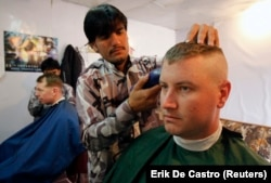 Warga Afghanistan memotong rambut tentara AS dari Batalyon ke-2, Divisi Infanteri ke-35, Satuan Tugas Kaktus di sebuah pangkas rambut di Provinsi Kunar, Afghanistan timur 13 Maret 2012. (Foto: REUTERS/Erik De Castro)