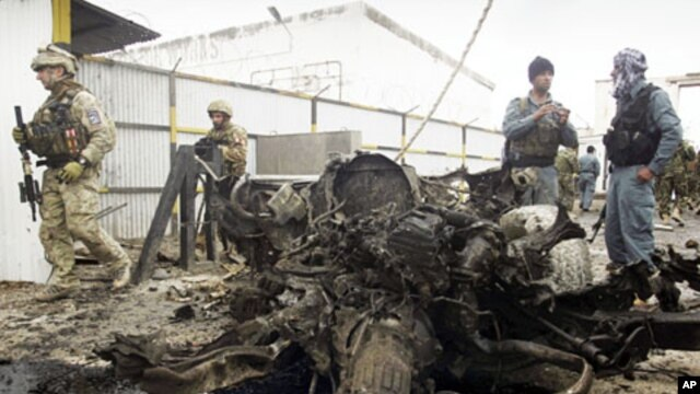 Afghan policemen (R) and foreign soldiers (L) with the NATO- led International Security Assistance Force (ISAF) inspect the scene of a suicide attack in Herat, west of Kabul,  Nov. 3, 2011