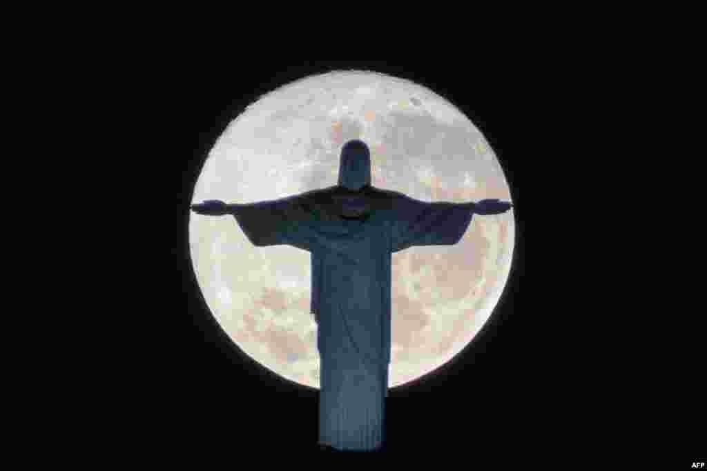 គេមើលឃើញស្រមោលនៃរូបសំណាក Christ the Redeemer ឈរទល់នឹងព្រះច័ន្ទពេញវង់នៅក្នុងក្រុង Rio de Janeiro ប្រទេសប្រេស៊ីល។