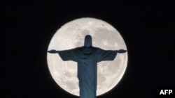 FILE - The silhouette of the statue of Christ the Redeemer atop Corcovado hill stands out against the full moon in Rio de Janeiro, Brazil, on July 19, 2016.