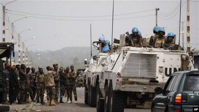 United Nations soldiers talk to forces loyal to Alassane Ouattara as they drive through a republican forces operating base on the outskirts of Abidjan, Ivory Coast, April 9, 2011
