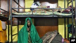 A homeless woman rests inside a shelter for homeless women and children managed by a non-governmental organization in New Delhi, January 6, 2011