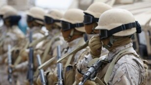 FILE - Saudi troops stand at attention at their base in Yemen's southern port city of Aden, Sept. 28, 2015.