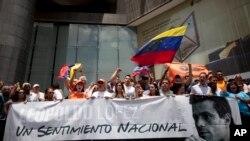 Những người ủng hộ nhà lãnh đạo đối lập đang bị giam Leopoldo Lopez cầm biểu ngữ và hình ông bên ngoài trụ sở Chương trình Phát triển Liên Hiệp Quốc ở Caracas Venezuela