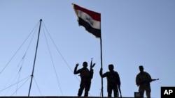 FILE - Iraqi soldiers plant the national flag over a government building in Ramadi, Dec. 21, 2015.