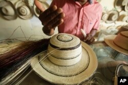 In this Dec. 16, 2017 photo, Reinaldo Quiros explains the confection of a traditional Panamanian pintao hat in La Pintada, Panama