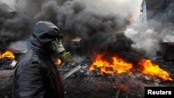 在基辅,一位支持与欧盟融合的乌克兰示威者走过防暴警察与示威者冲突的现场。(2014年1月23日)