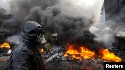 Một người biểu tình đi trong khu vực vừa xảy ra xô xát với cảnh sát trong thủ đô Kyiv, 23/1/14