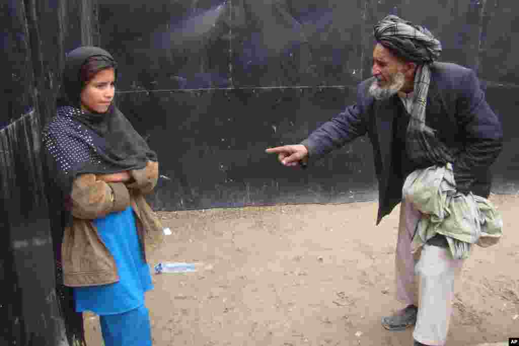 Abdul Ghafar talks to her daughter known as Spozhmai in protective custody in Lashkargah, capital of Helmand province, south of Afghanistan. The father of the girl, who police say was part of a botched suicide bomb attack, said he's afraid the Taliban will kill him and his daughter if they return to their village.
