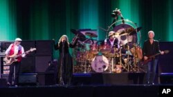 John McVie, from left, and Stevie Nicks and Lindsey Buckingham of Fleetwood Mac perform at the Isle of Wight Festival, in Newport, Isle of Wight, England, June 14, 2015.
