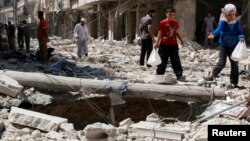 A girl gestures as she walks on the rubble of collapsed buildings at a site hit by what activists said was a barrel bomb dropped by forces loyal to Syria's President Bashar al-Assad in Aleppo's district of al-Sukari, June 17, 2014.