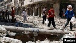 Cư dân đi trên đống đổ nát của tòa nhà bị sập sau vụ không kích của lực lượng trung thành với ông Assad tại thành phố Aleppo, ngày 17/6/2014.