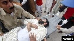 Equipas de socorro assistem um homem ferido em Peshawar, Paquistão