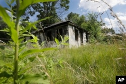FILE - An abandoned house with an overgrown lot is seen in Brightmoor, a neighborhood on Detroit's northwest side, July 19, 2013.
