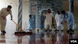 Jamaah membersihkan lantai masjid setelah serangan bom bunuh diri di Darra Adam Khel, selatan Peshawar, Pakistan.