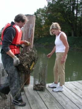 Chris Judy with Sally Ackridge on her backyard pier where she cares for 38 cages of baby oysters.