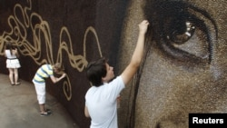 Assistants put the finishing touches on artwork project in Russia's Gorky Park, June 26, 2012.