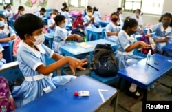 Students apply hand sanitiser in a class at the Viqarunnisa Noon School & College after the government has withdrawn restrictions on educational institutions following a decrease in the number of cases of COVID-19 in Dhaka, Bangladesh, Sept. 12, 2021.