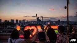 La gente toma fotografías de una réplica de la Estatua de la Libertad en el paseo marítimo de Odaiba en Tokio el 22 de julio de 2021, en vísperas del inicio de los Juegos Olímpicos de Tokio 2020. (Foto de Philip FONG / AFP)