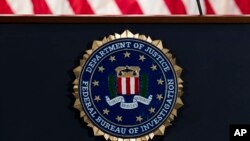 FILE - In this June 14, 2018, file photo, the FBI seal is seen before a news conference at FBI headquarters in Washington. The FBI is grappling with a seemingly endless cycle of money laundering schemes that law enforcement officials say they're…