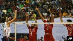 USA volleyball player Aron Russell, left, smashes the ball against, from left, Iran's Mir Saeid Marouflakrani, Mohammad Mousavi Eraghi and Milad Ebadipour Ghara during Men's Volleyball World League, at the Azadi (Freedom) stadium in Tehran, Iran, June 19