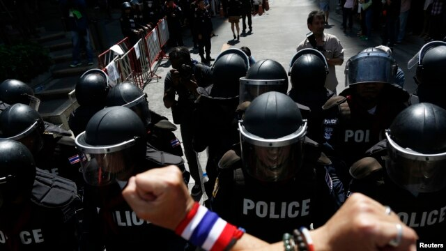 An anti-government protester gestures towards riot police outside the headquarters of the ruling Puea Thai Party of Prime Minister Yingluck Shinawatra in Bangkok, Nov. 29, 2013.