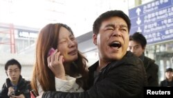 សមាជិកគ្រួសារ (អាវស) របស់អ្នកដំណើរម្នាក់នៅលើយន្តហោះអាកាសចរណ៍ម៉ាឡេស៊ីជើងហោះហើរលេខ MH370 យំខណៈអ្នកស្រីទូរស័ព្ទនៅអាកាសយានដ្ឋានអន្តរជាតិរដ្ឋធានីប៉េកាំងកាលពីថ្ងៃទី៨ ខែមីនា ឆ្នាំ២០១៤។