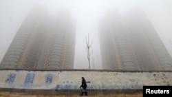 一名戴口罩的婦女走過中國河北邯鄲的大樓旁。(2019年1月12日)