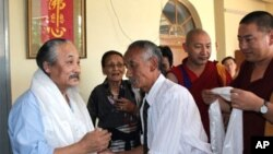 Lhasang Tsering (right) presenting traditional Tibetan white scarves to Amnye Machen's Academic Director Tashi Tsering (left).