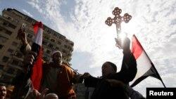 Kahire'deki Tahrir Meydanı'ndaki göstericilere elindeki haçla katılan bir Mısırlı Kıpti