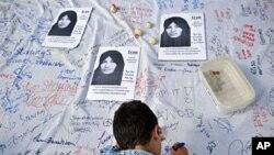 Un jeune garçon signant une pétition contre la lapidation, devant des photos de l'Iranienne Sakineh Mohammadi Ashtiani, condamnée à ce supplice par le régime de Téhéran