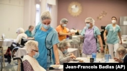 Nurses give food during lunch at a nursing home in Kaysesberg, eastern France on Monday Dec. 21, 2020. (AP Photo/Jean-Francois Badias)