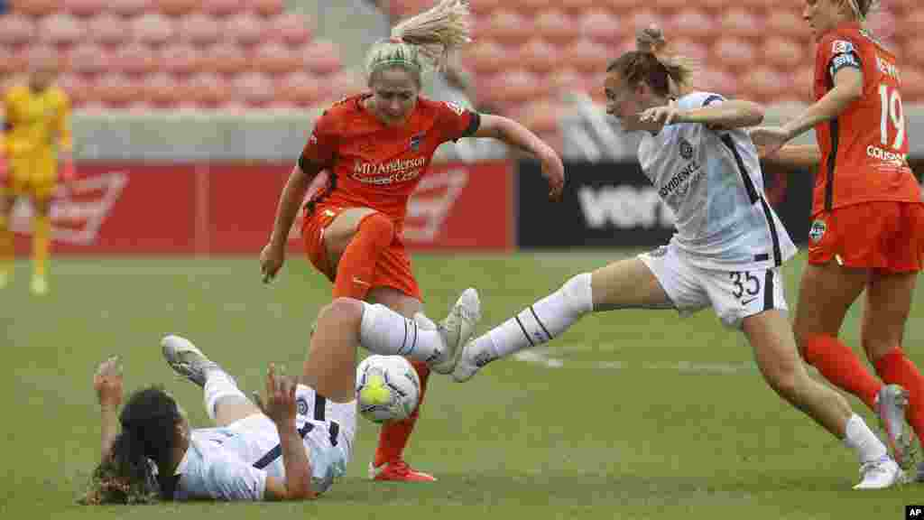 Houston Dash midfielder Bri Visalli, center, battles with Portland Thorns' Rocky Rodriguez, left, and Gabby Seiler (35) during the second half of an NWSL Challenge Cup soccer semifinal match Wednesday, July 22, 2020, in Sandy, Utah. (AP Photo/Rick Bowmer)