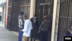Abanye abantu abahlolisisa okwenzakala eHarvest House eHarare. (Photo: Rutendo Mawere)