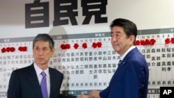 PM Jepang Shinzo Abe (kanan) pemimpin partai Demokratik Liberal Jepang, bersama Wapres Masahiko Komura di markas besar partai tersebut di Tokyo, 22 Oktober 2017.