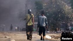 2013年3月22日在缅甸密铁拉地区的骚乱期间,人们携带武器。