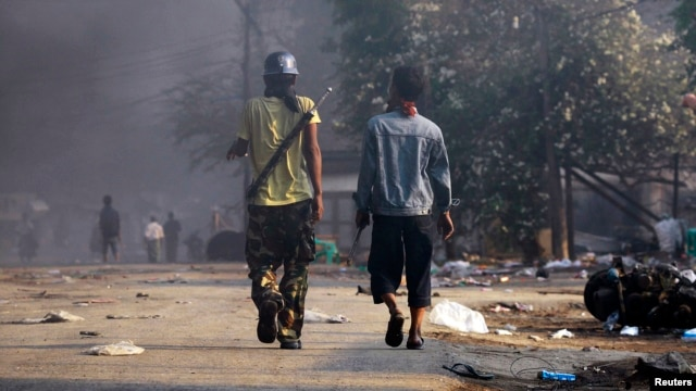 People carry weapons during riots in Meikhtila, Burma, Mar. 22, 2013.