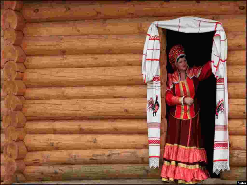 روس کے مقامی گاؤں میں ایک خاتون روایتی لباس پہنے دروازے کے باہر کھڑی ہے۔