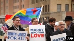 FILE - Spencer Geiger, Carl Johansen and Robert Robert Roman protest for equal marriage outside the Walter E. Hoffman U.S. Courthouse as oral arguments in the case of Bostic v Rainey proceed, Feb. 4, 2014.
