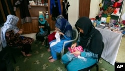 FILE - Victims of violence sew at a shelter operated by the Humanitarian Assistance for the Women and Children of Afghanistan, an NGO, in Kabul, Afghanistan, April 5, 2017.