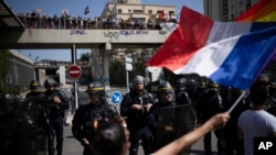 Protesters face French riot police during a demonstration against vaccine passports in Marseille, France, Aug. 14, 2021.