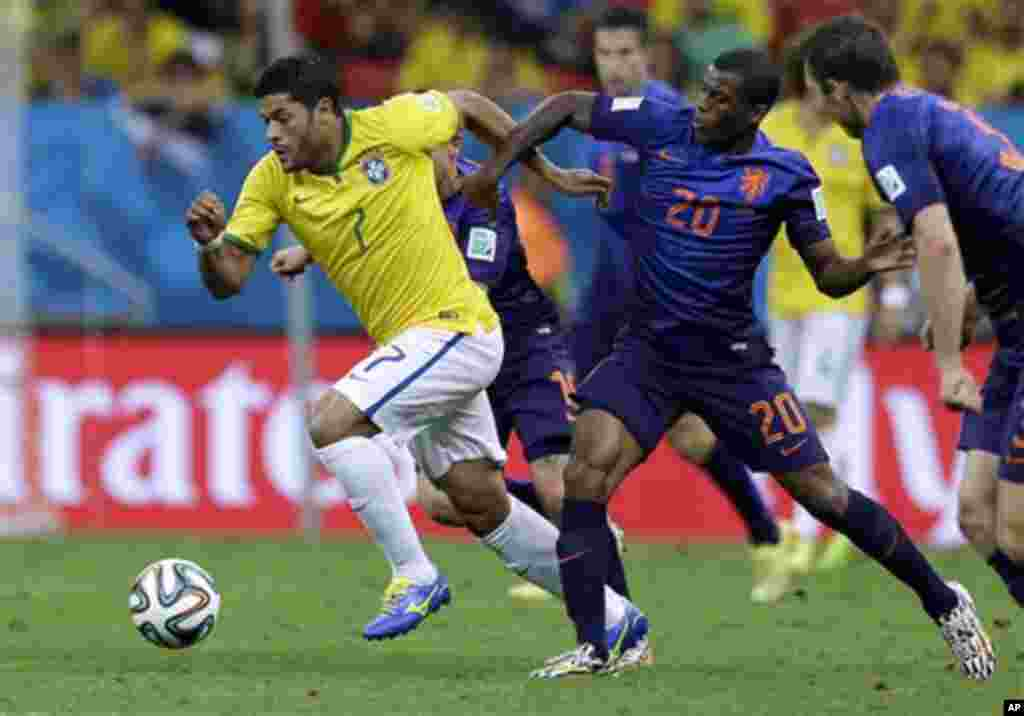 Brazil's Hulk, left, is held by Netherlands' Georginio Wijnaldum during the World Cup third-place soccer match between Brazil and the Netherlands at the Estadio Nacional in Brasilia, Brazil, Saturday, July 12, 2014. (AP Photo/Natacha Pisarenko)