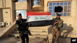 عراقی فوجی موصل کی ایک عمارت کے سامنے اپنے پرچم کے ساتھ ۔ 21 اکتوبر 2016